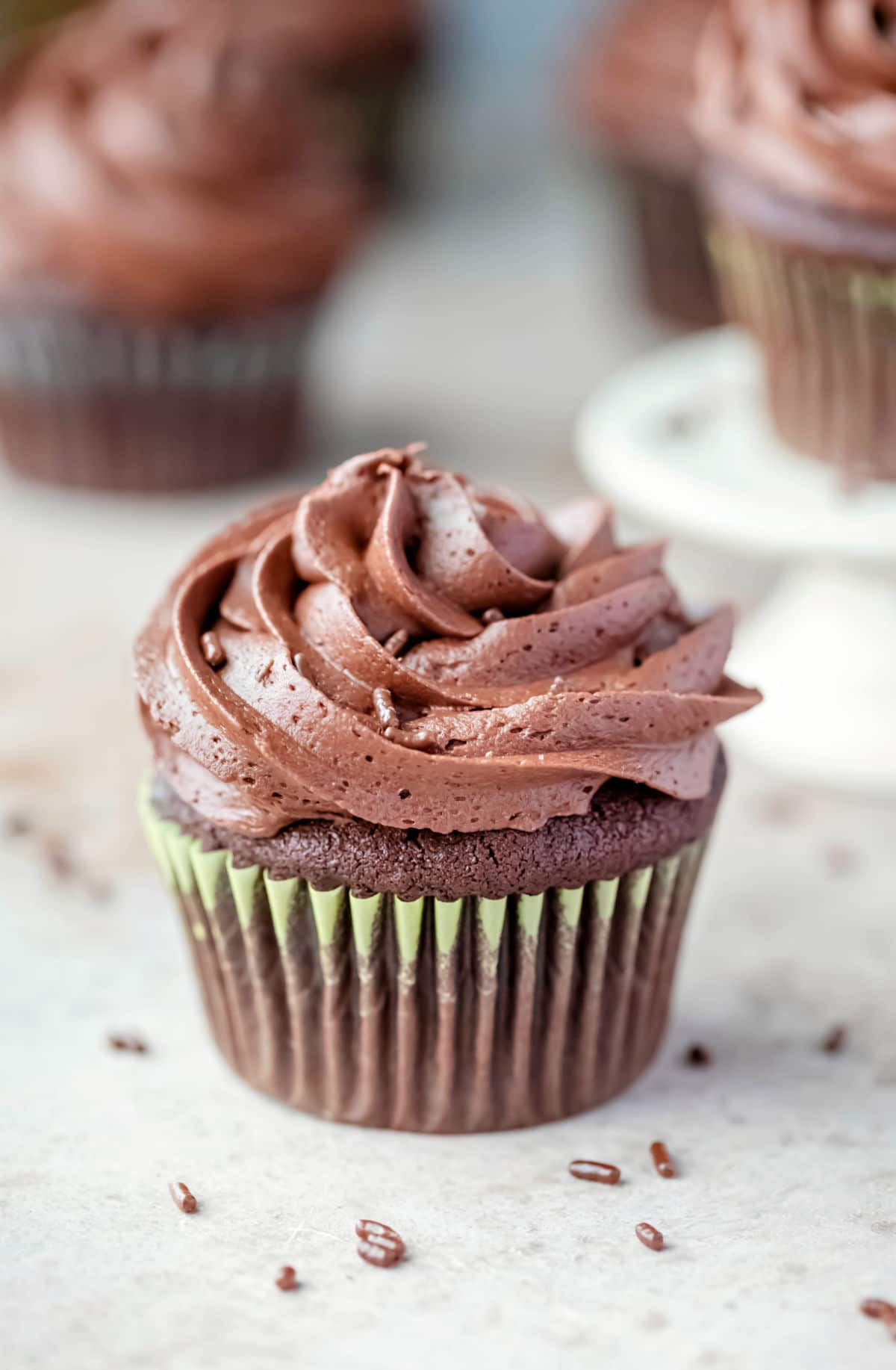 chocolate cupcake topped with chocolate frosting next to other chocolate cupcakes.