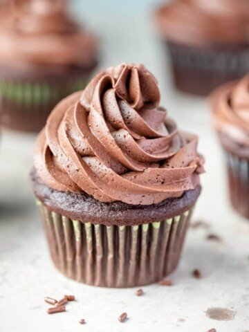 Chocolate cupcake with chocolate frosting next to chocolate sprinkles.