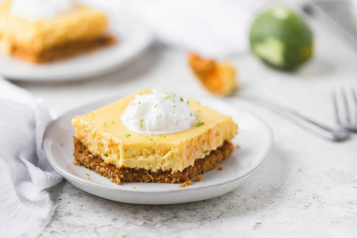 Key lime pie bar next to a fork with a bite of pie on it.