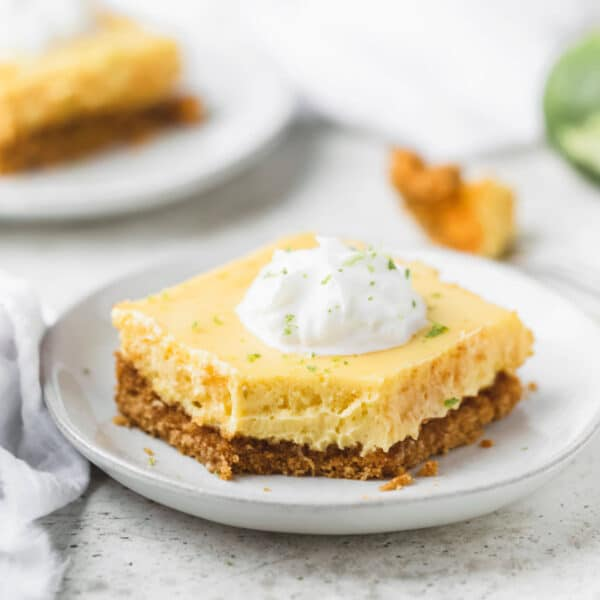 Square photo of key lime pie bar on a white plate.