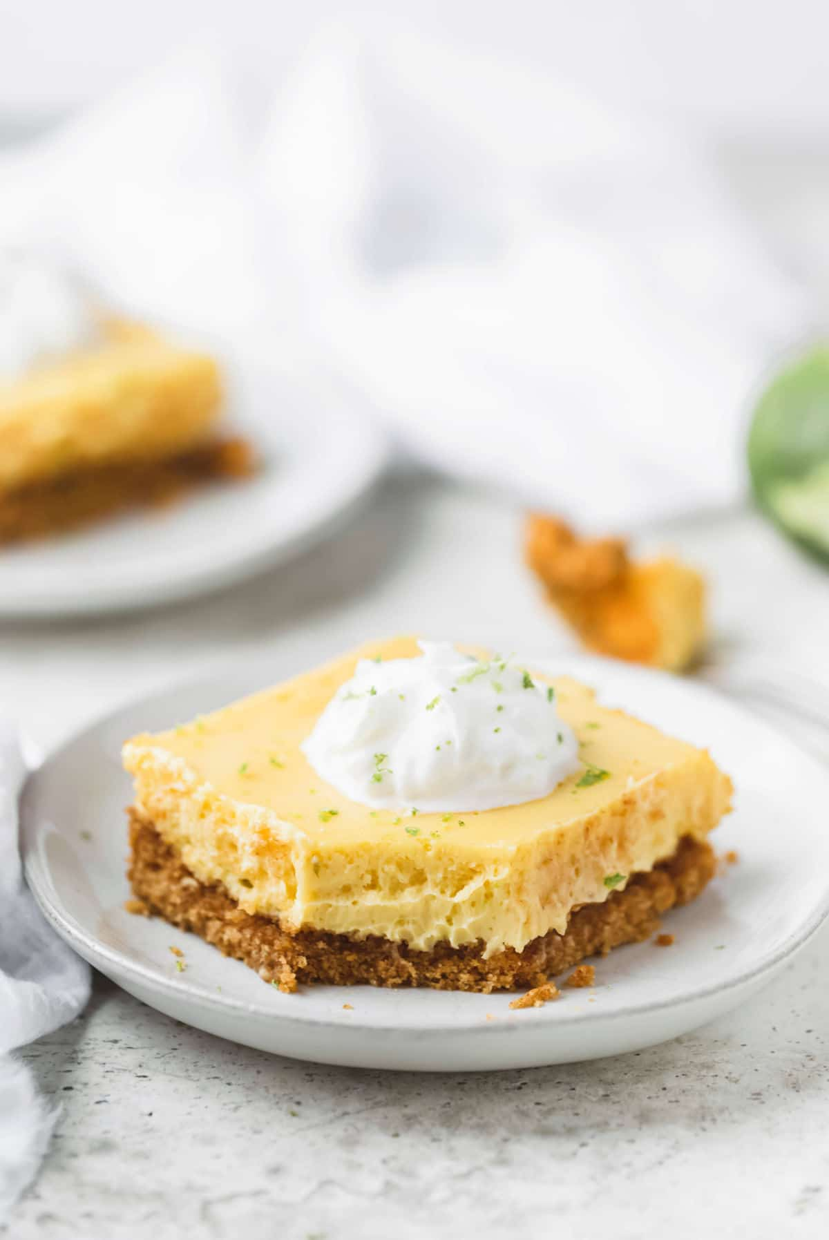 Piece of key lime pie bars topped with whipped cream and lime zest