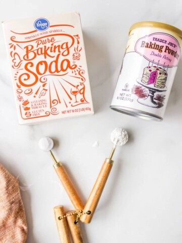 A box of baking soda next to a can of baking powder.