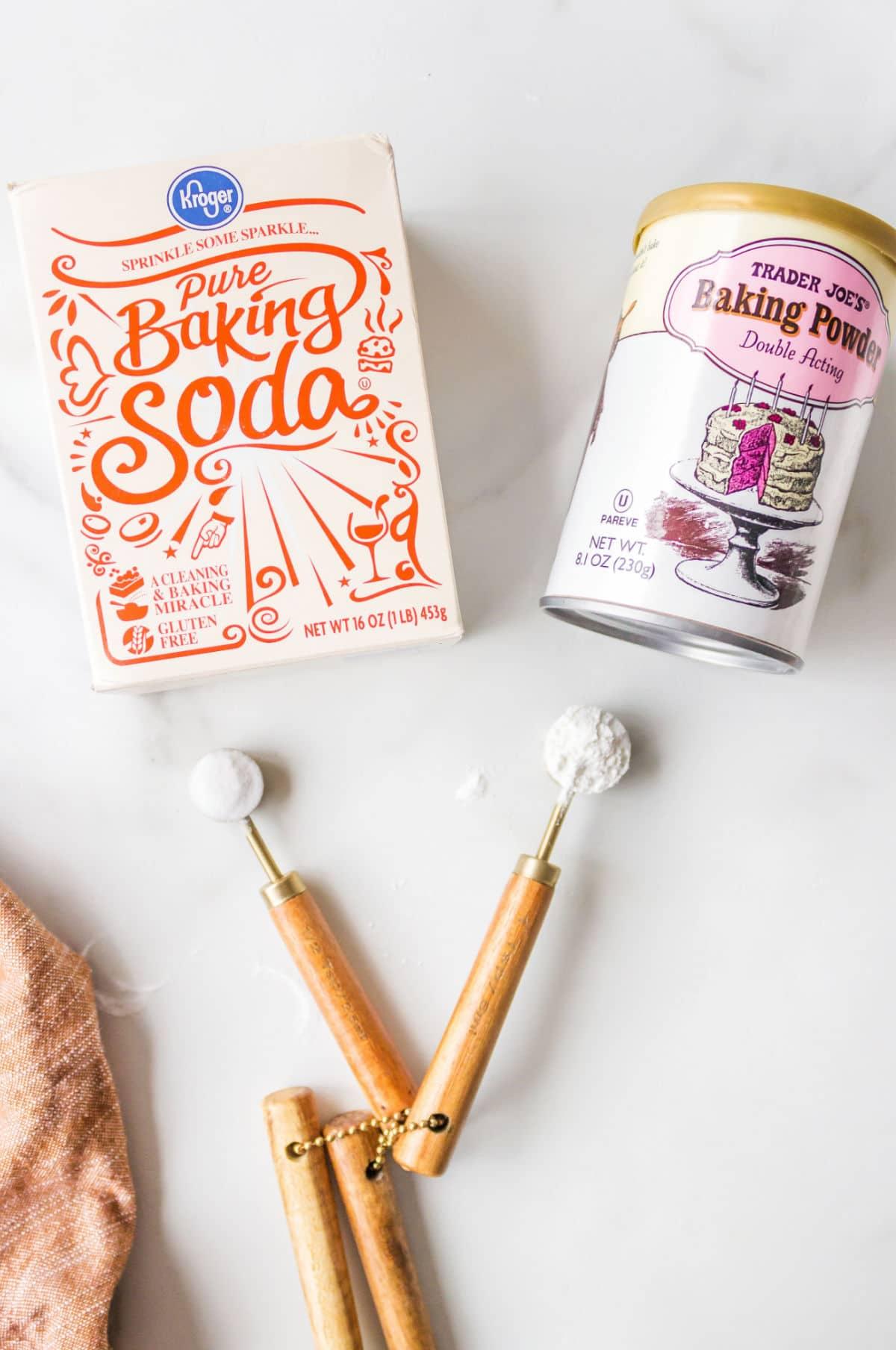 Box of baking soda next to a can of baking powder.
