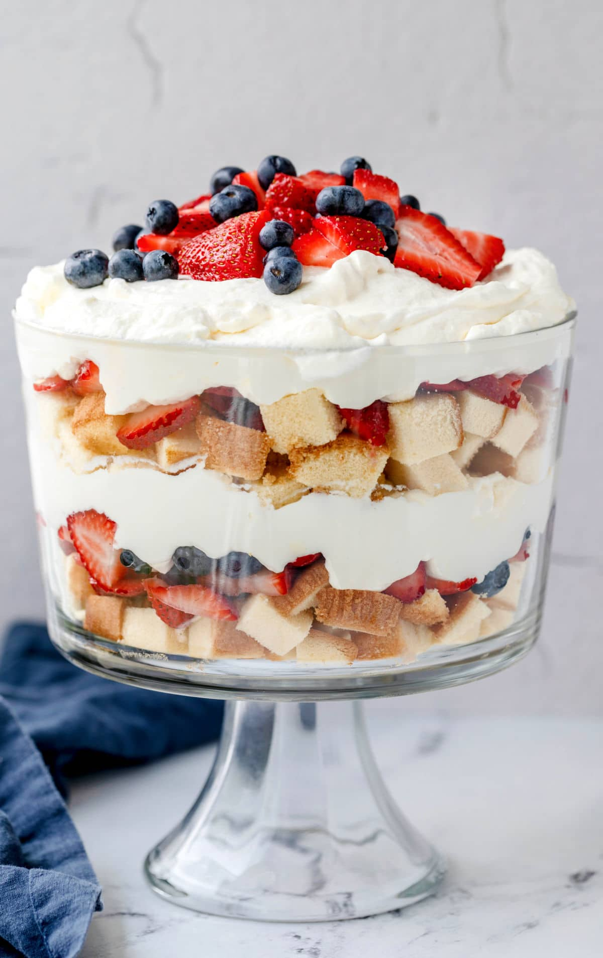 Layers of pound cake whipped cream and fresh berries in a trifle dish.