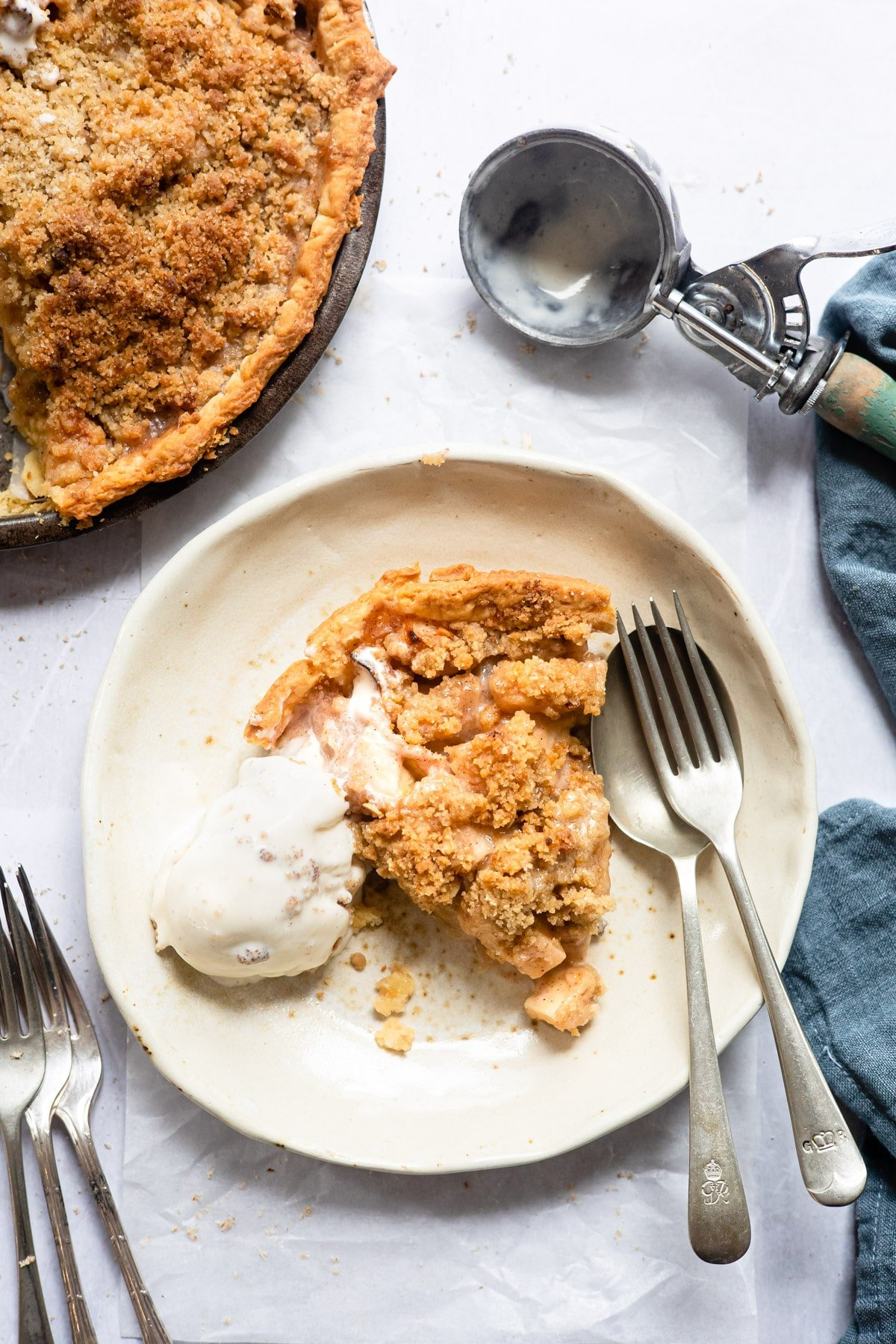 Slice of apple crumb pie next to a scoop of vanilla ice cream on a plate.