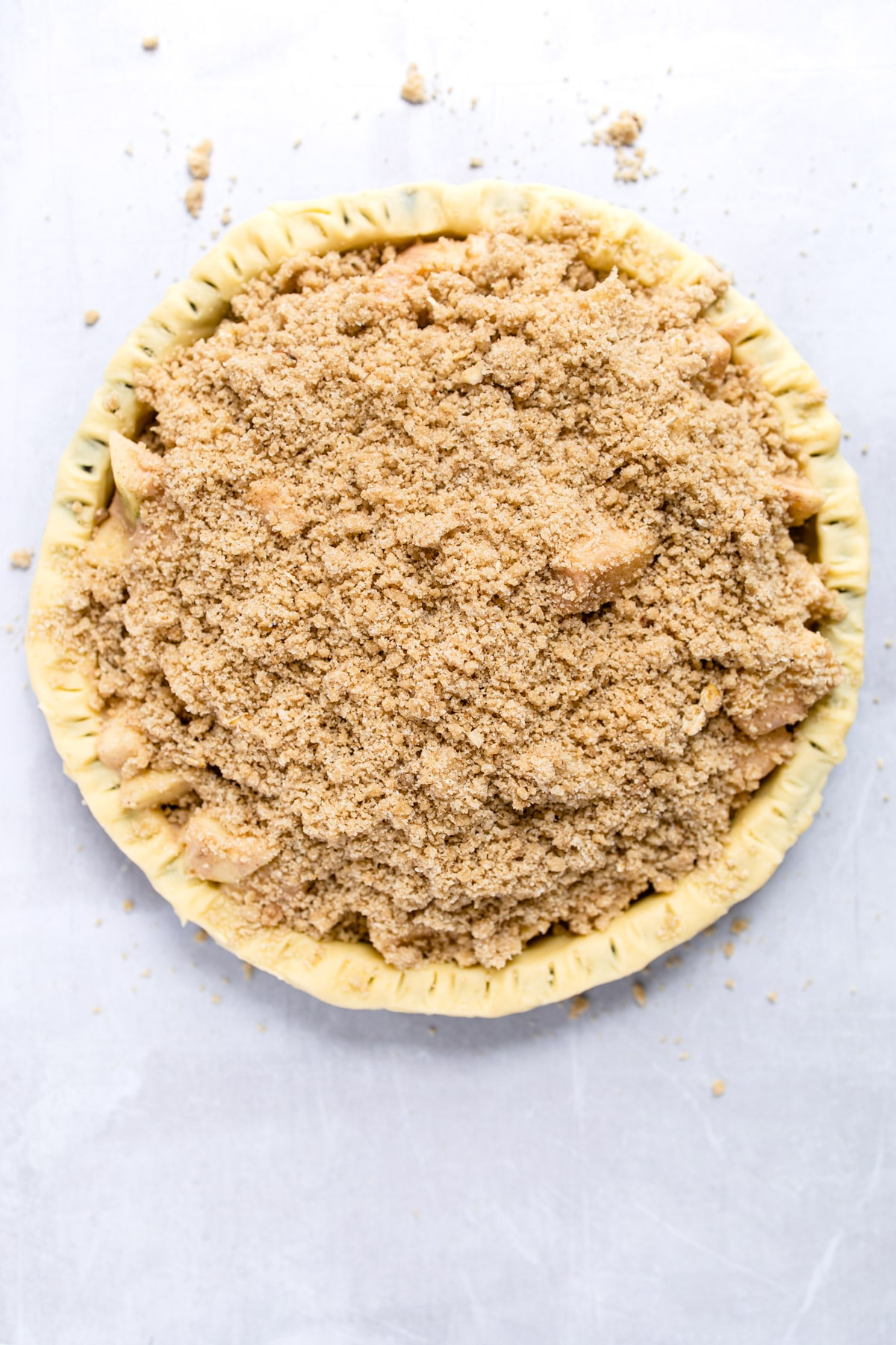 unbaked crumb topping on an unbaked apple crumb pie.