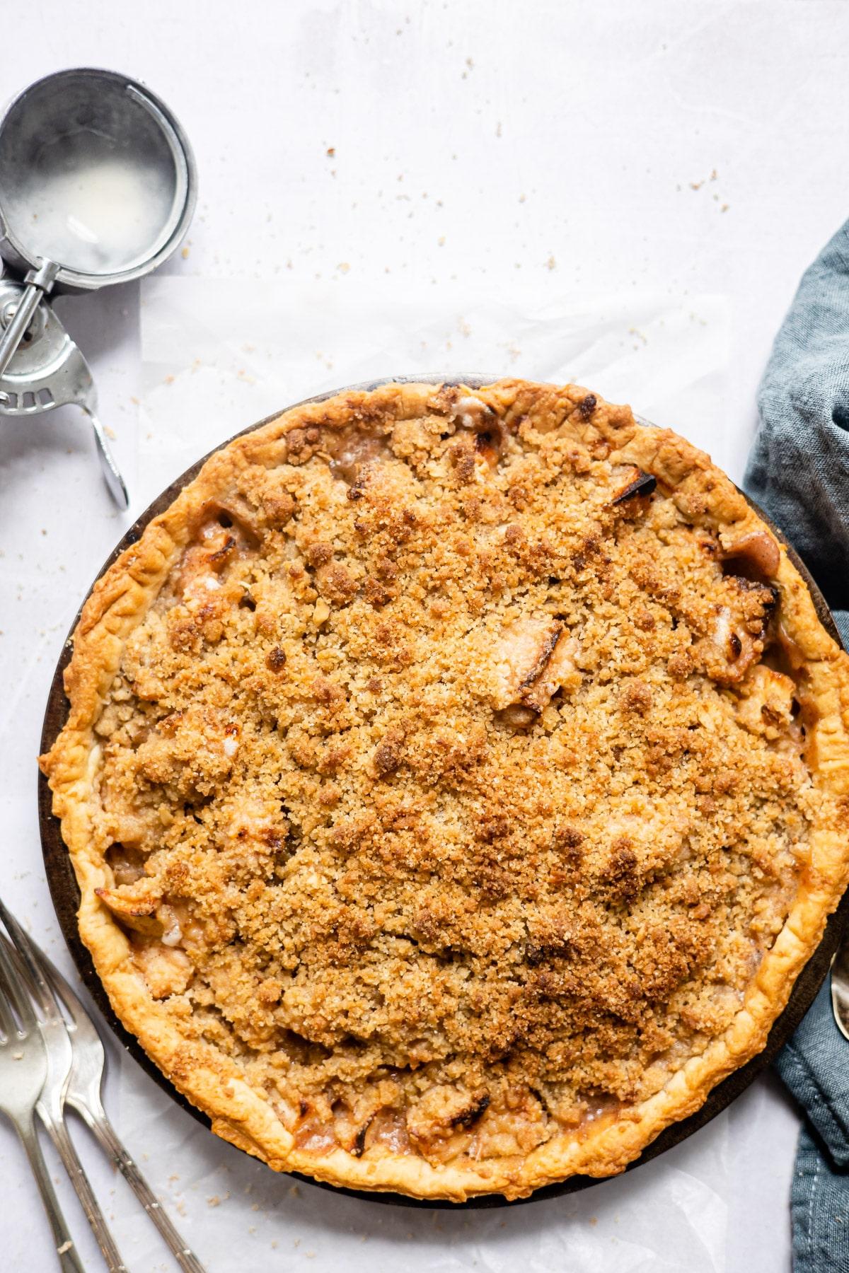Baked apple crumb pie next to an ice cream scoop.