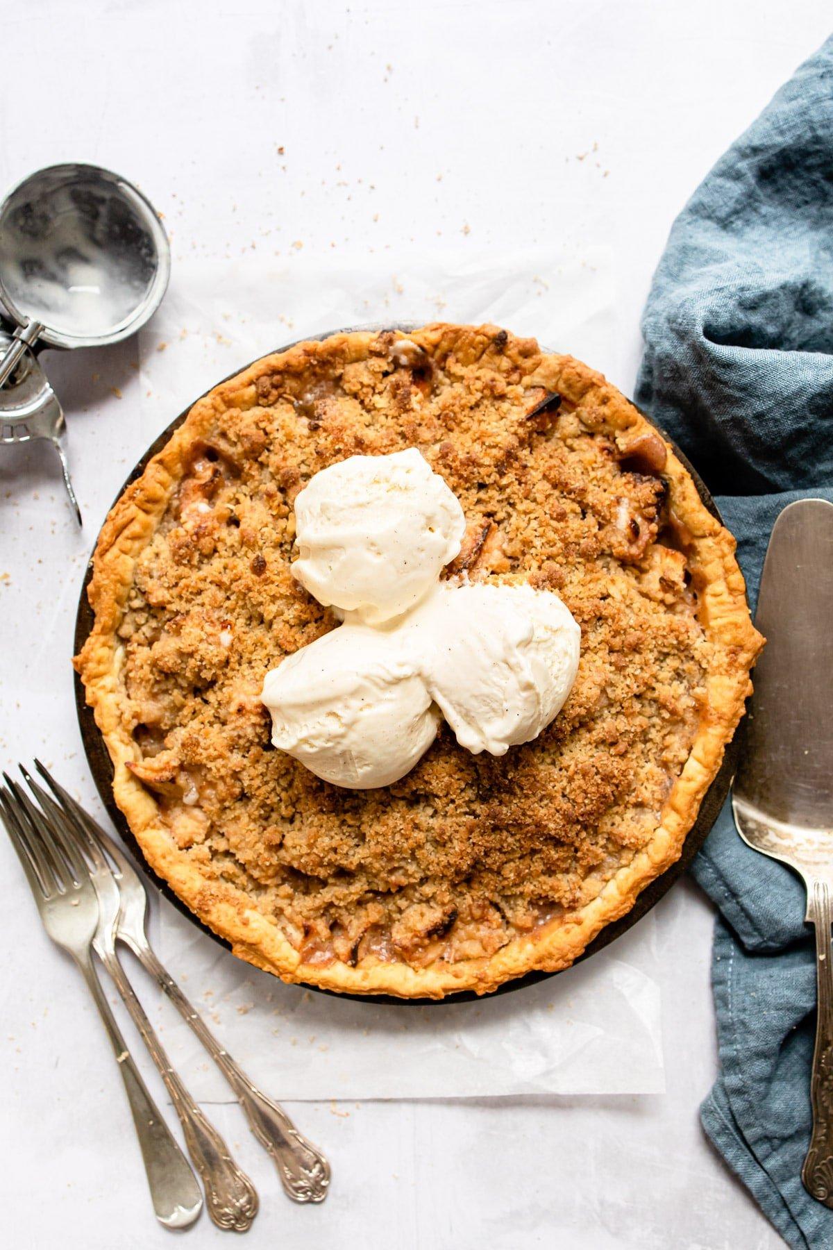 Three scoops of vanilla ice cream on an apple pie.