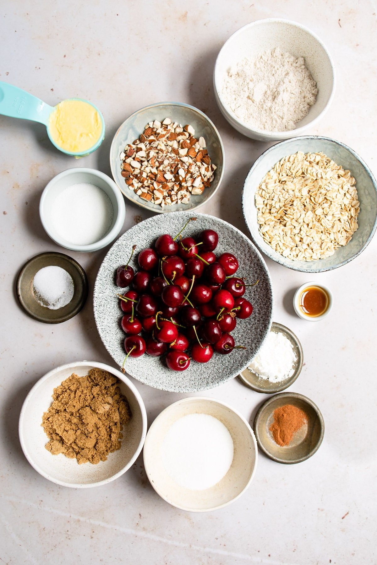 Ingredients for cherry crisp in bowls next to each other.