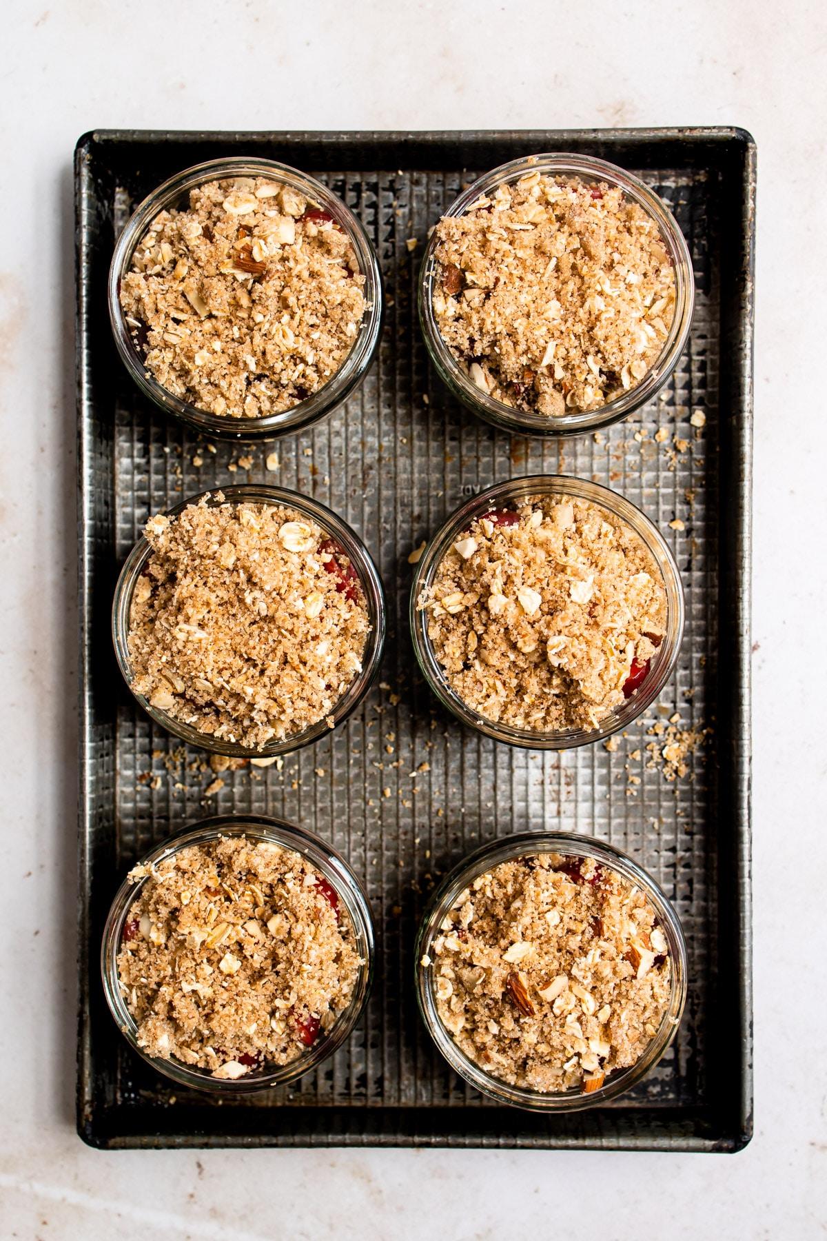 6 unbaked cherry crisps in ramekins on a baking sheet.