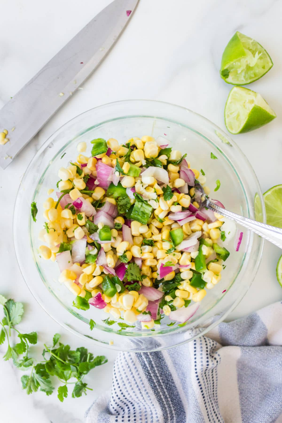 Corn salsa in a glass dish with fresh limes and fresh cilantro around it.