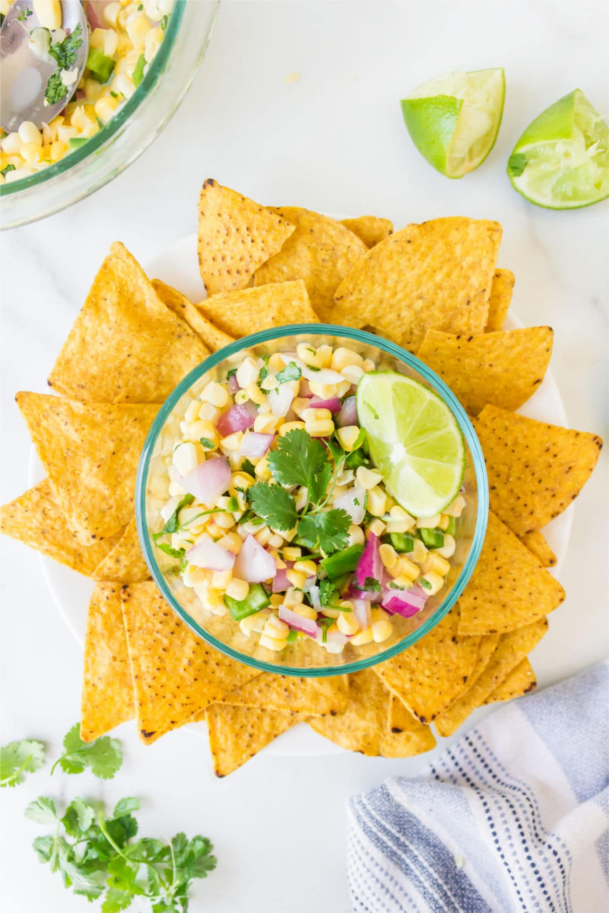 Dish of fresh corn salsa surrounded by tortilla chips.
