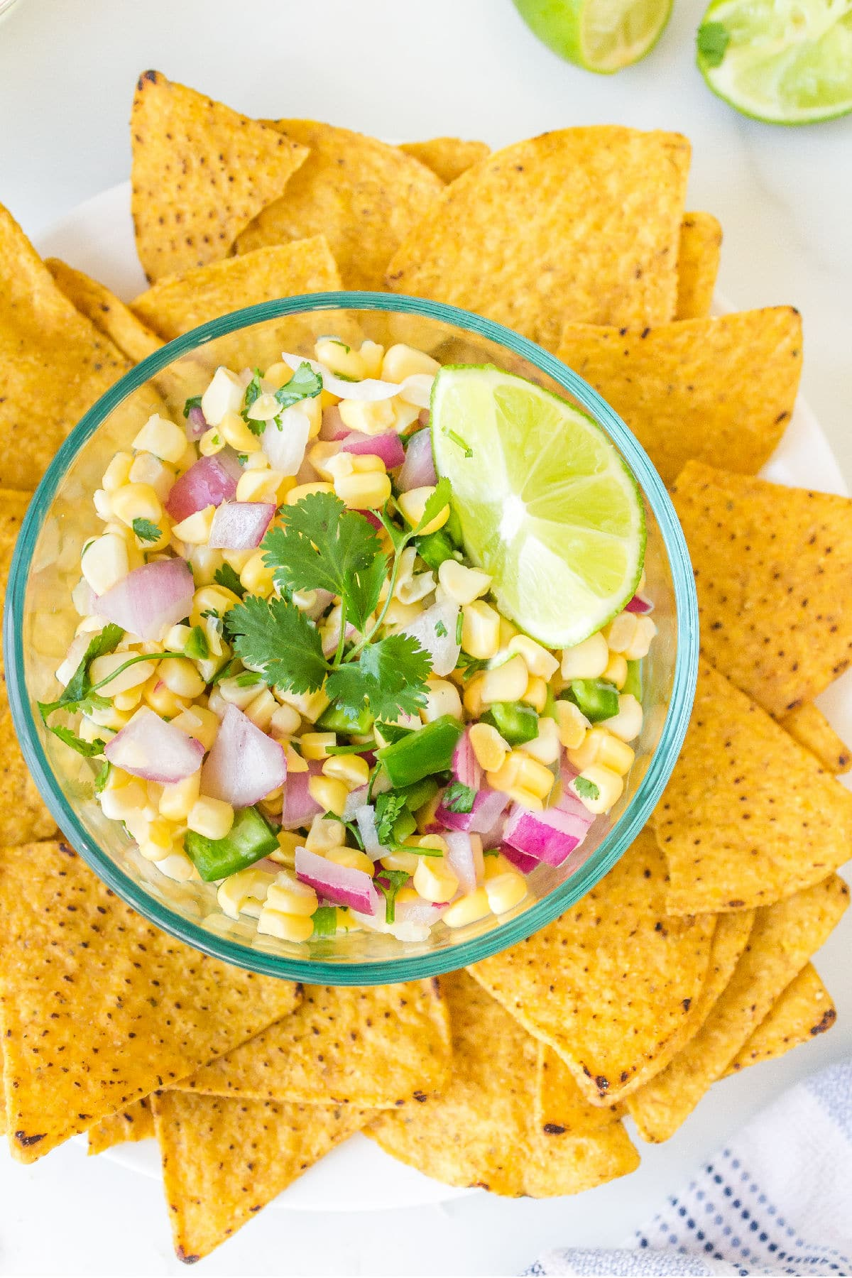 Glass bowl full of corn salsa topped with a lime wedge and fresh cilantro.