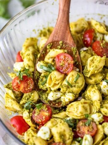 wooden spoon scooping pesto tortellini pasta salad.