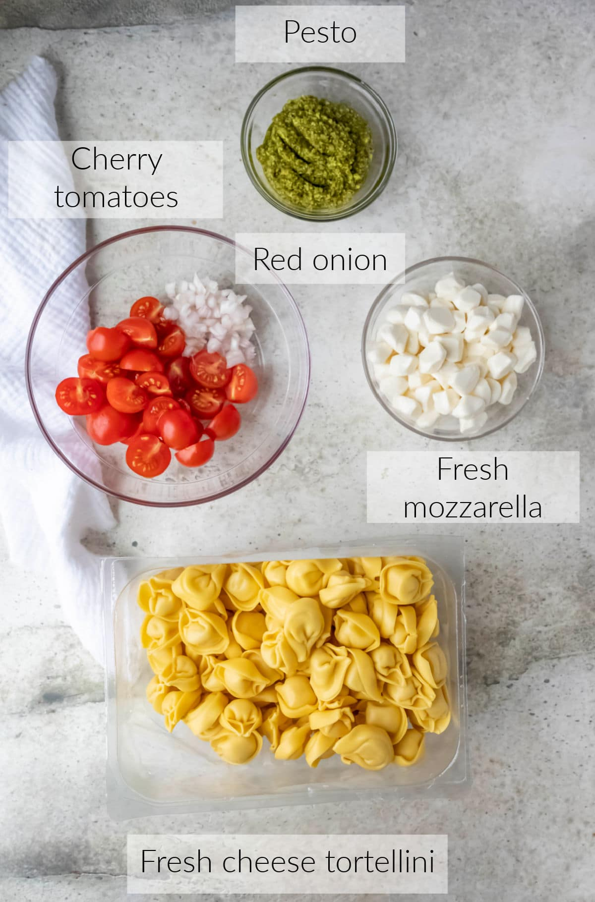 Labeled photo with pesto tortellini ingredients in dishes.