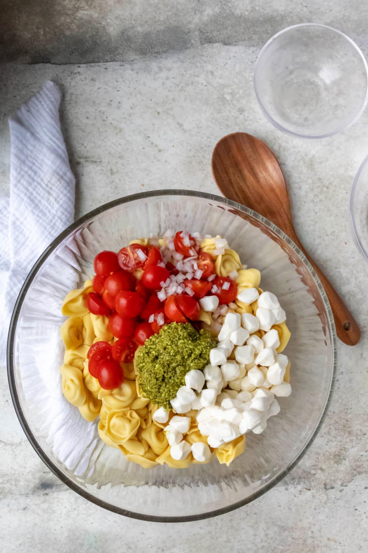 Pesto tortellini pasta salad ingredients in a glass mixing bowl.