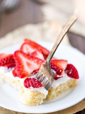 Fork taking a bite of strawberry shortcake bar.