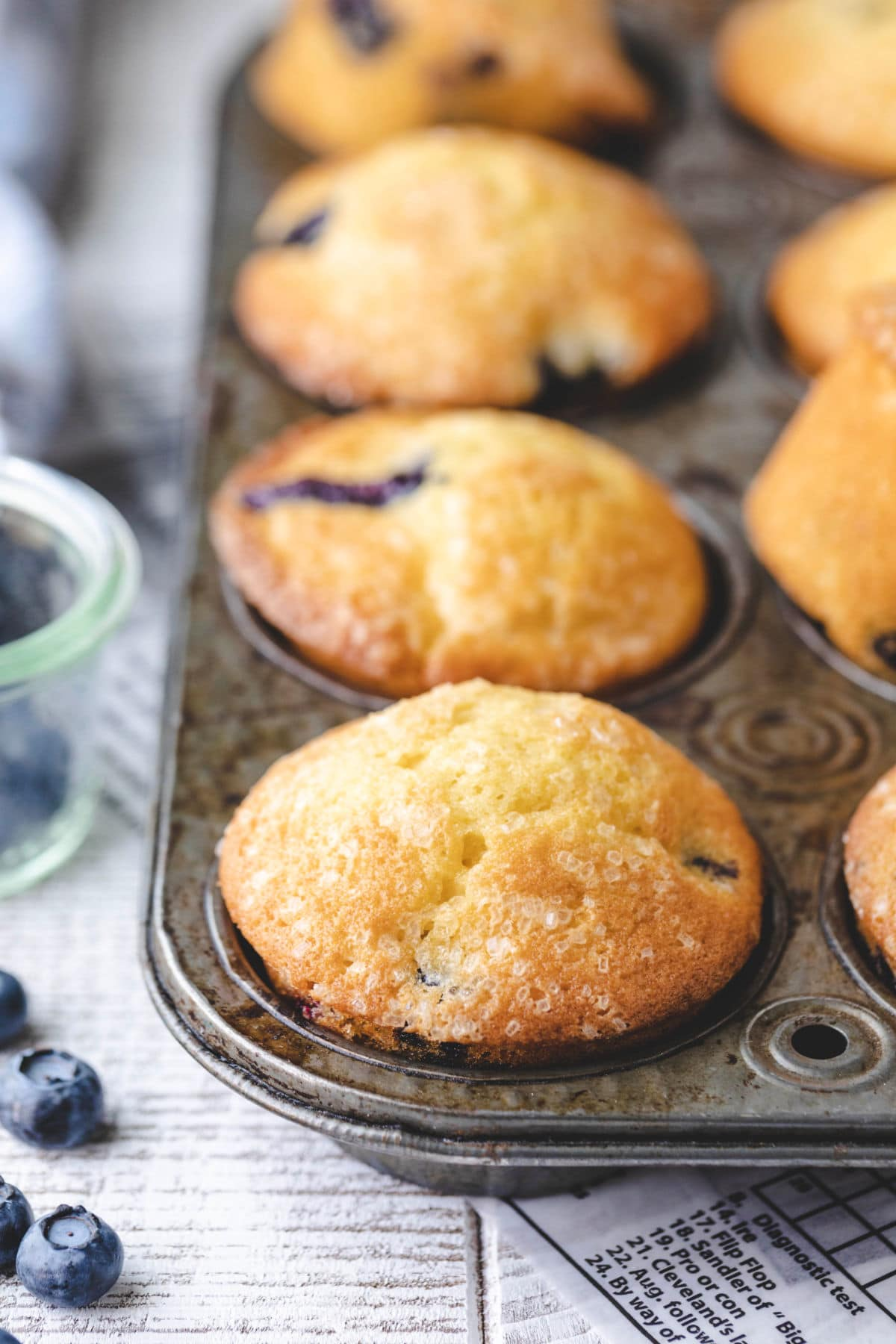 Bakery style blueberry muffins in a vintage muffin tin.