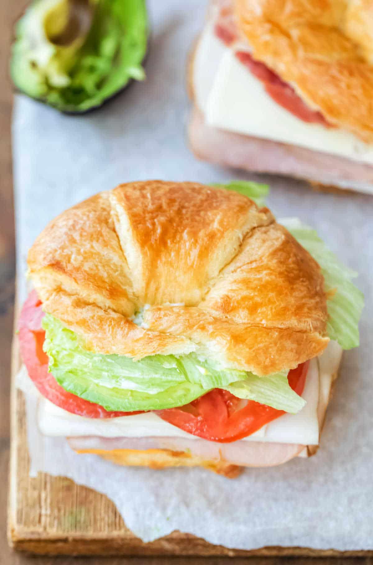 Overhead view of croissant sandwich on a piece of parchment paper.