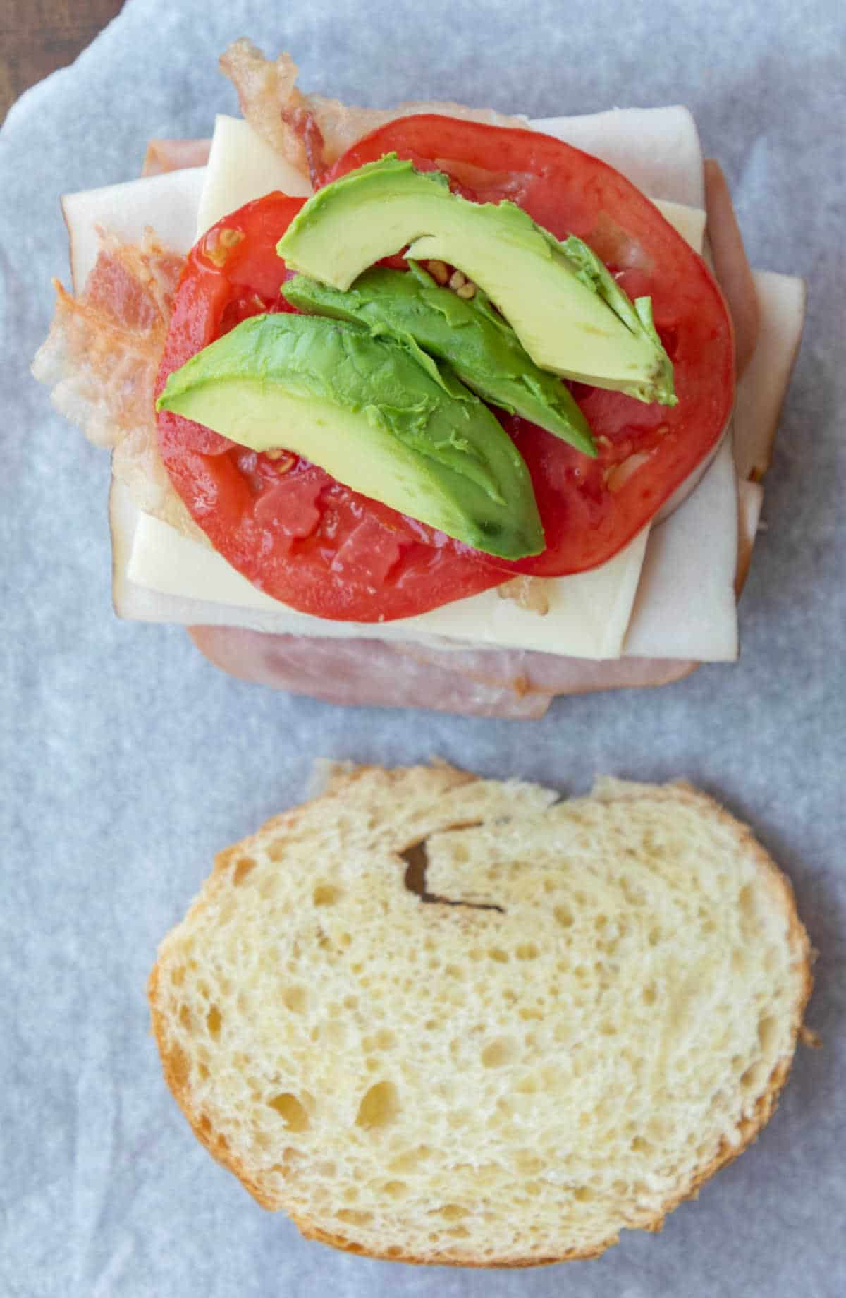 Slices of avocado and tomato on a croissant sandwich.