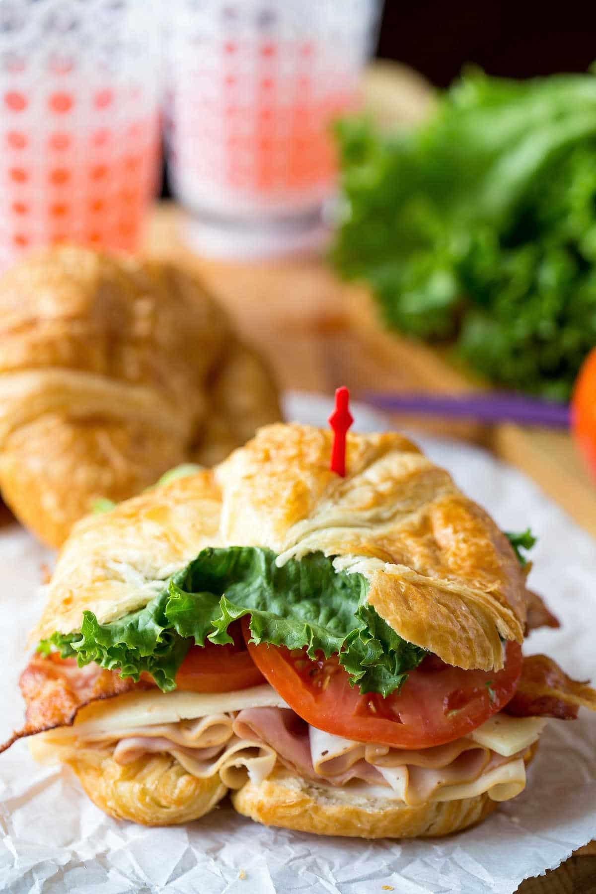 California club croissant sandwich on a piece of white parchment paper.