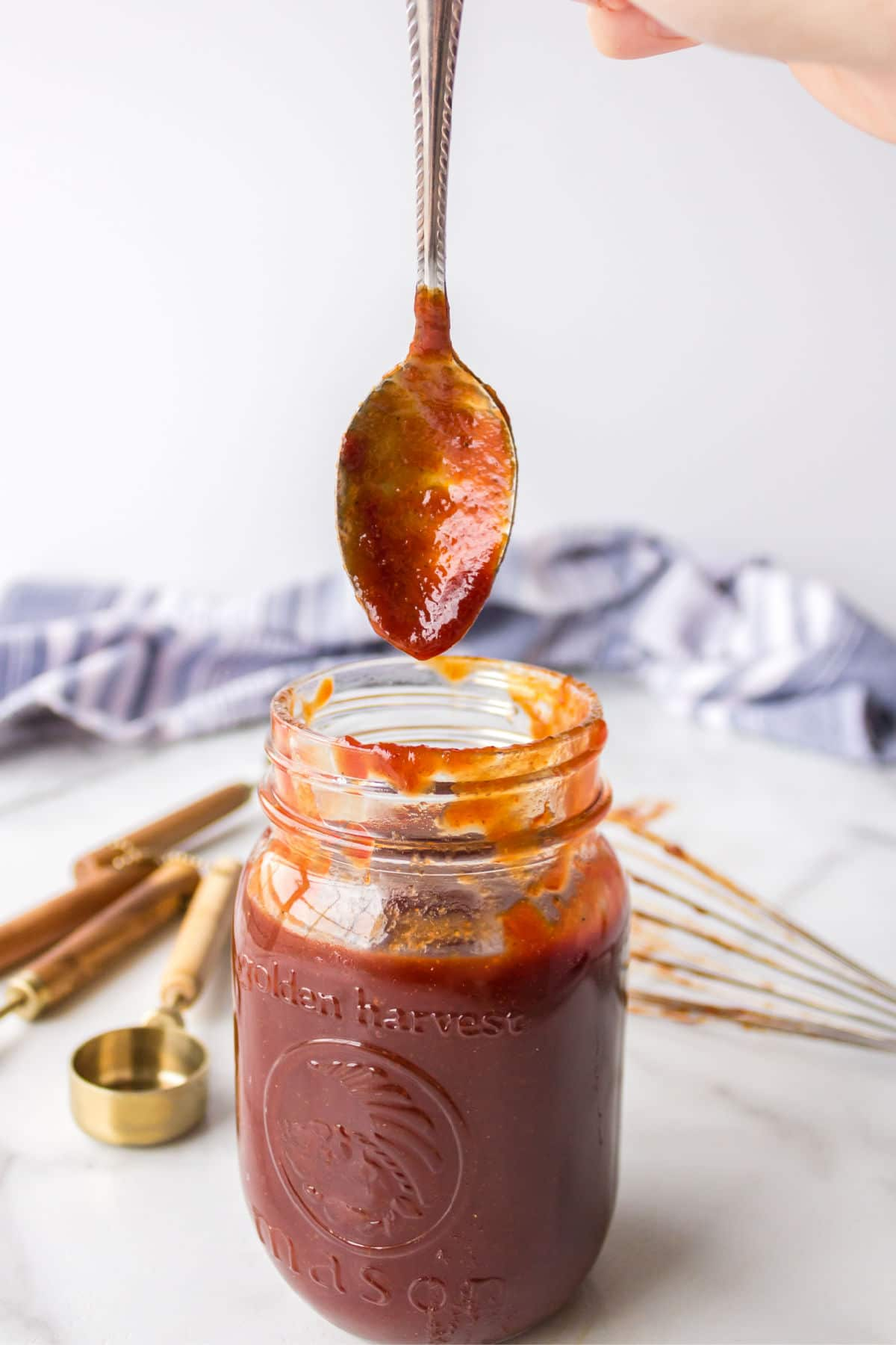 A spoon coming out of a jar of barbecue sauce.
