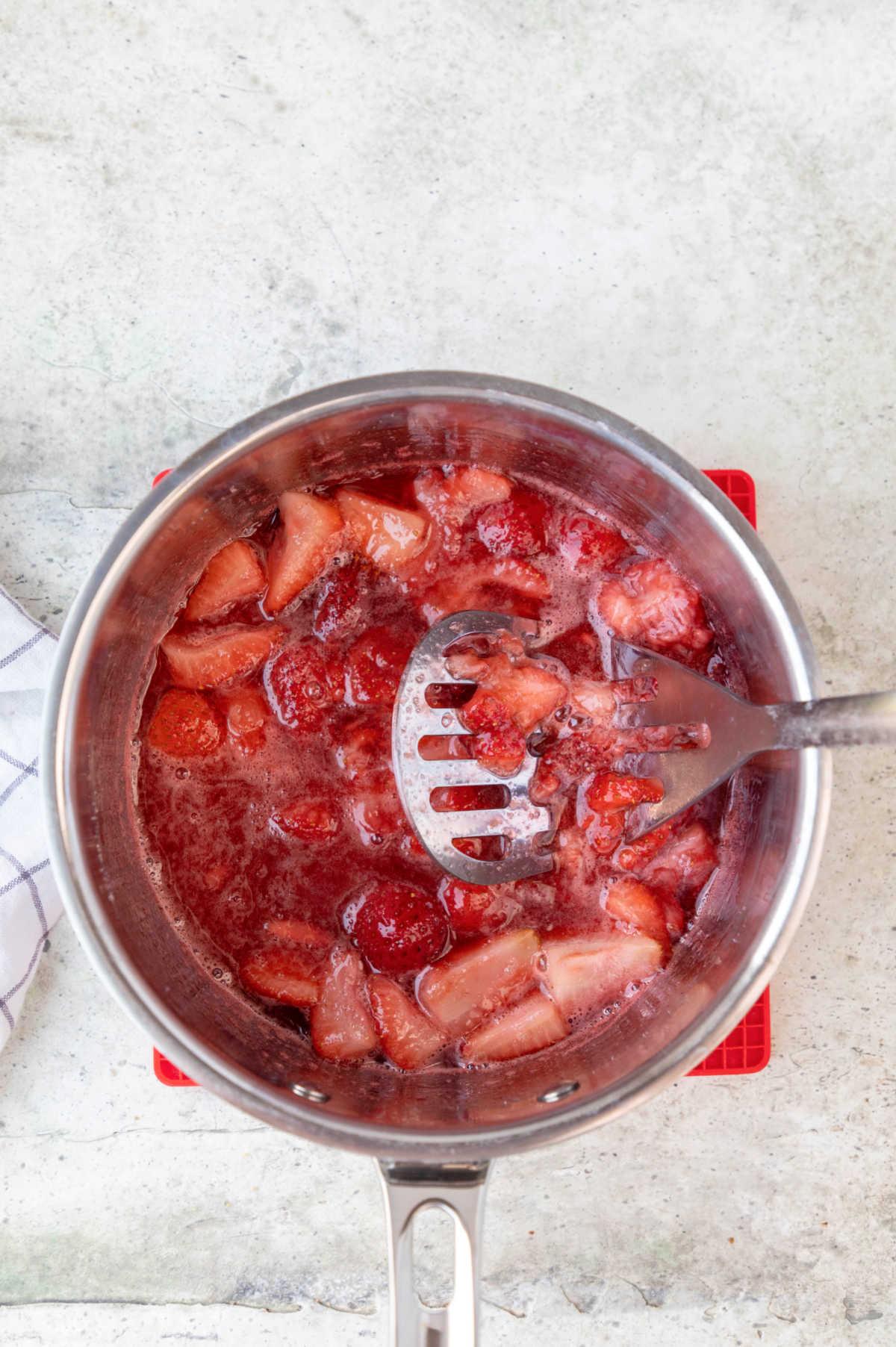 A potato masher mashing strawberries in a saucepan.