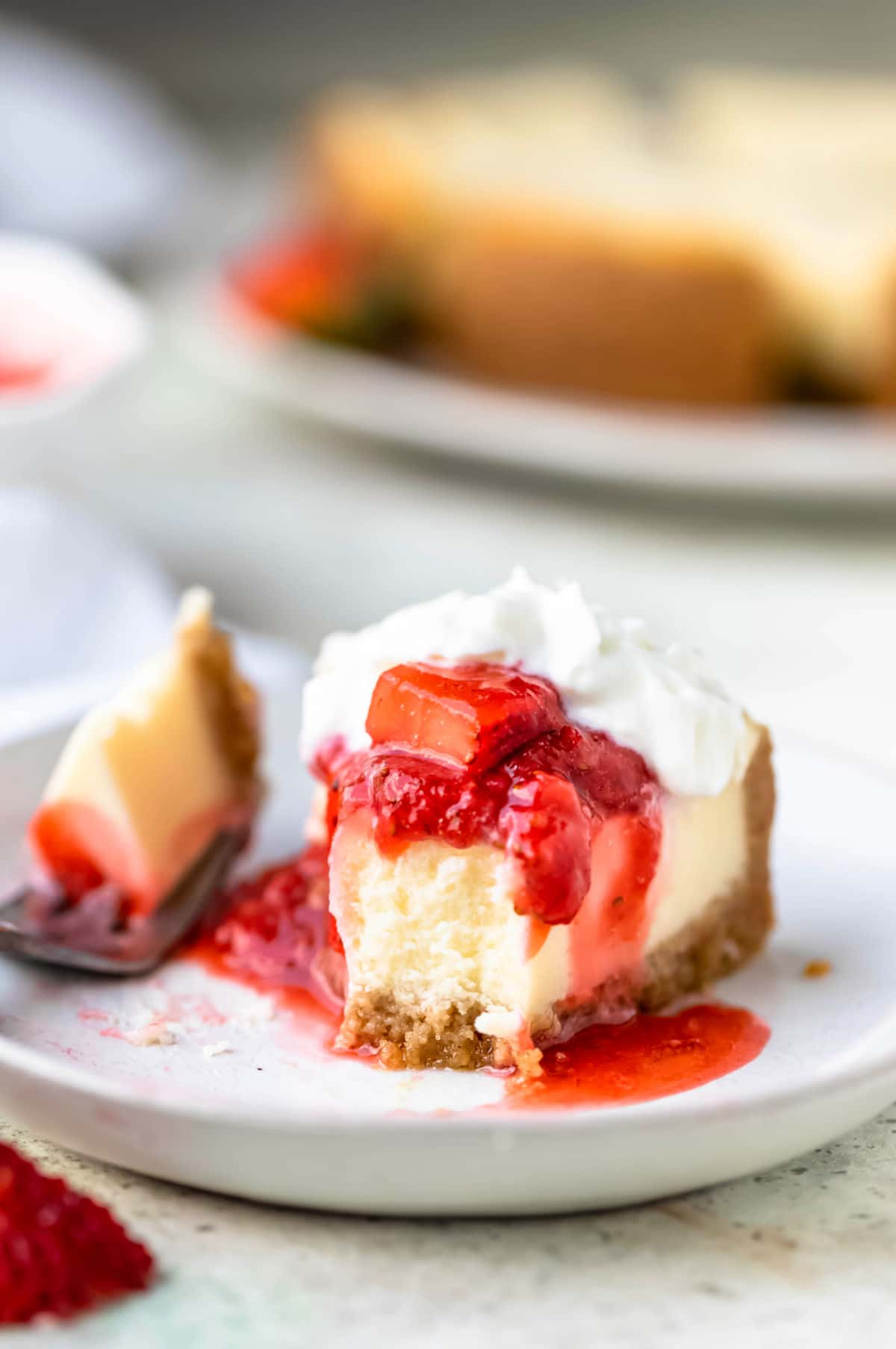 Strawberry topping on cheesecake with a bite out of the cheesecake.