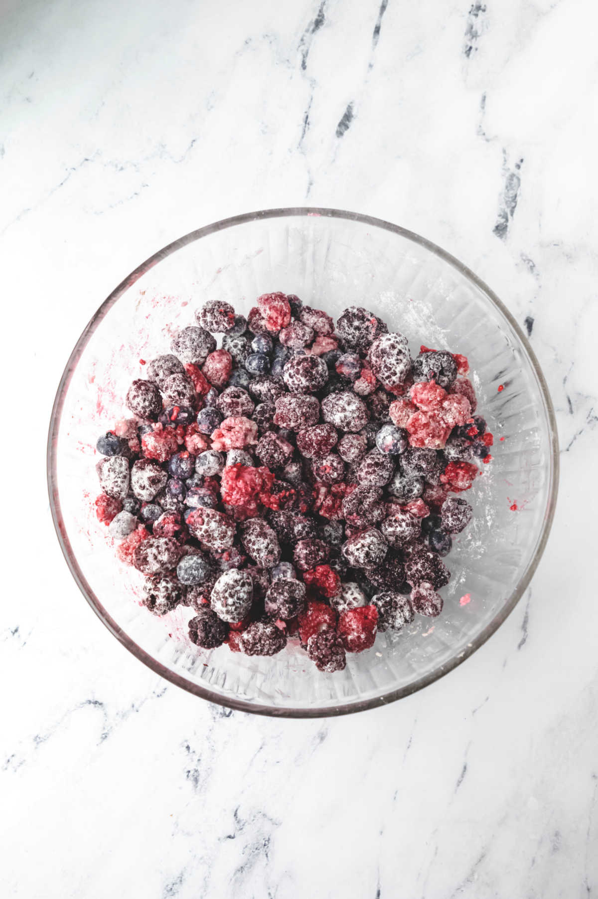 Raspberries blueberries and blackberries in a glass mixing bowl.