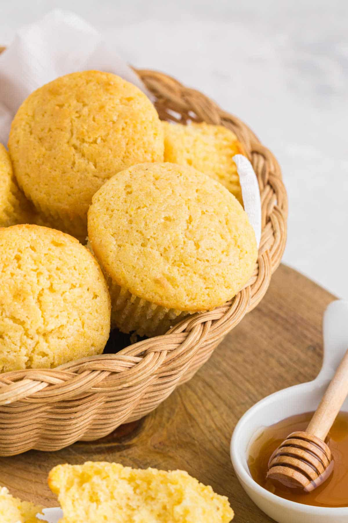Basket of cornbread muffins next to a dish of honey.