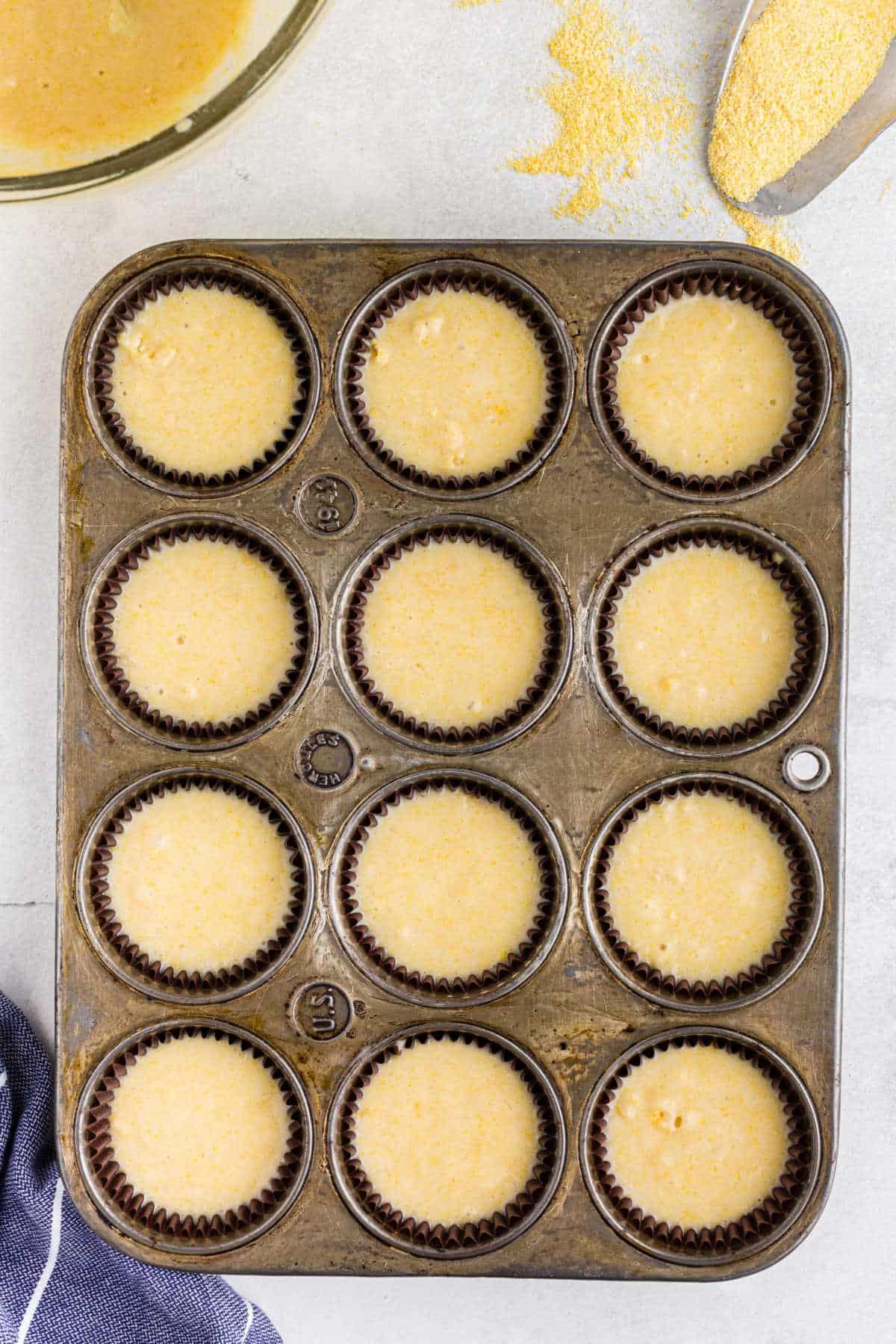 Cornbread muffin batter in a muffin tin.