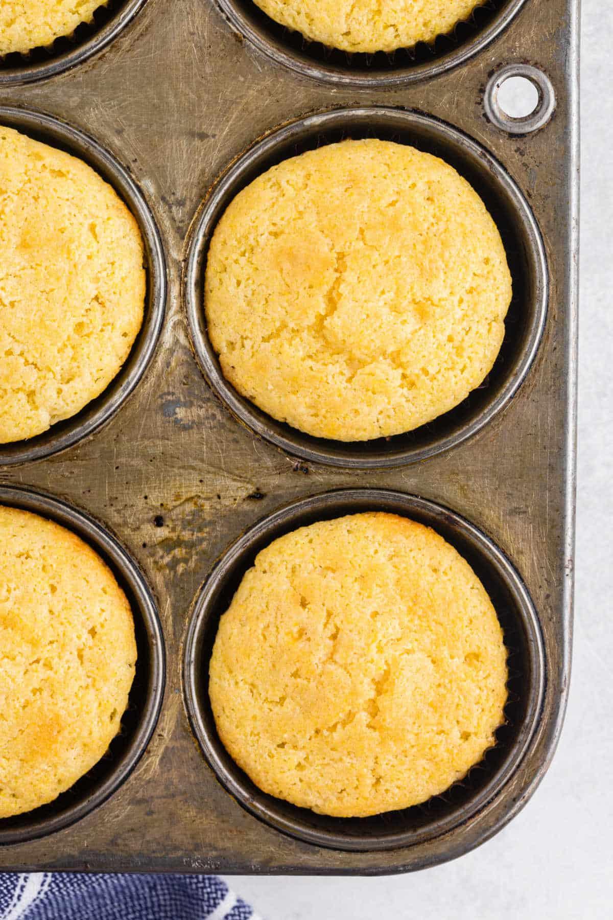 Baked cornbread muffins in a muffin tin.