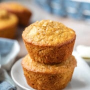 Two apple cinnamon oatmeal muffins stacked on a plate.