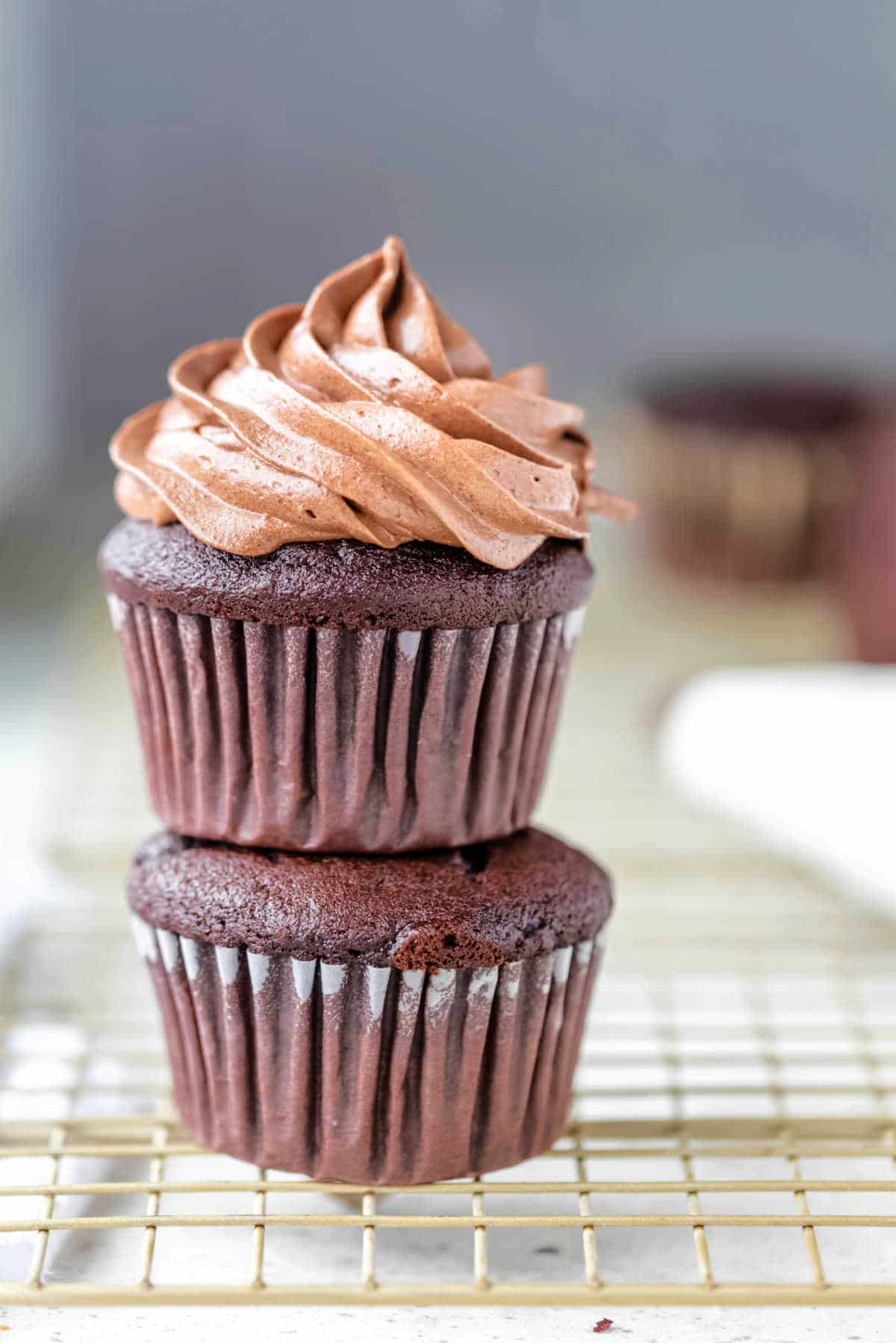 A frosted cupcake sitting on an unfrosted chocolate cupcake.