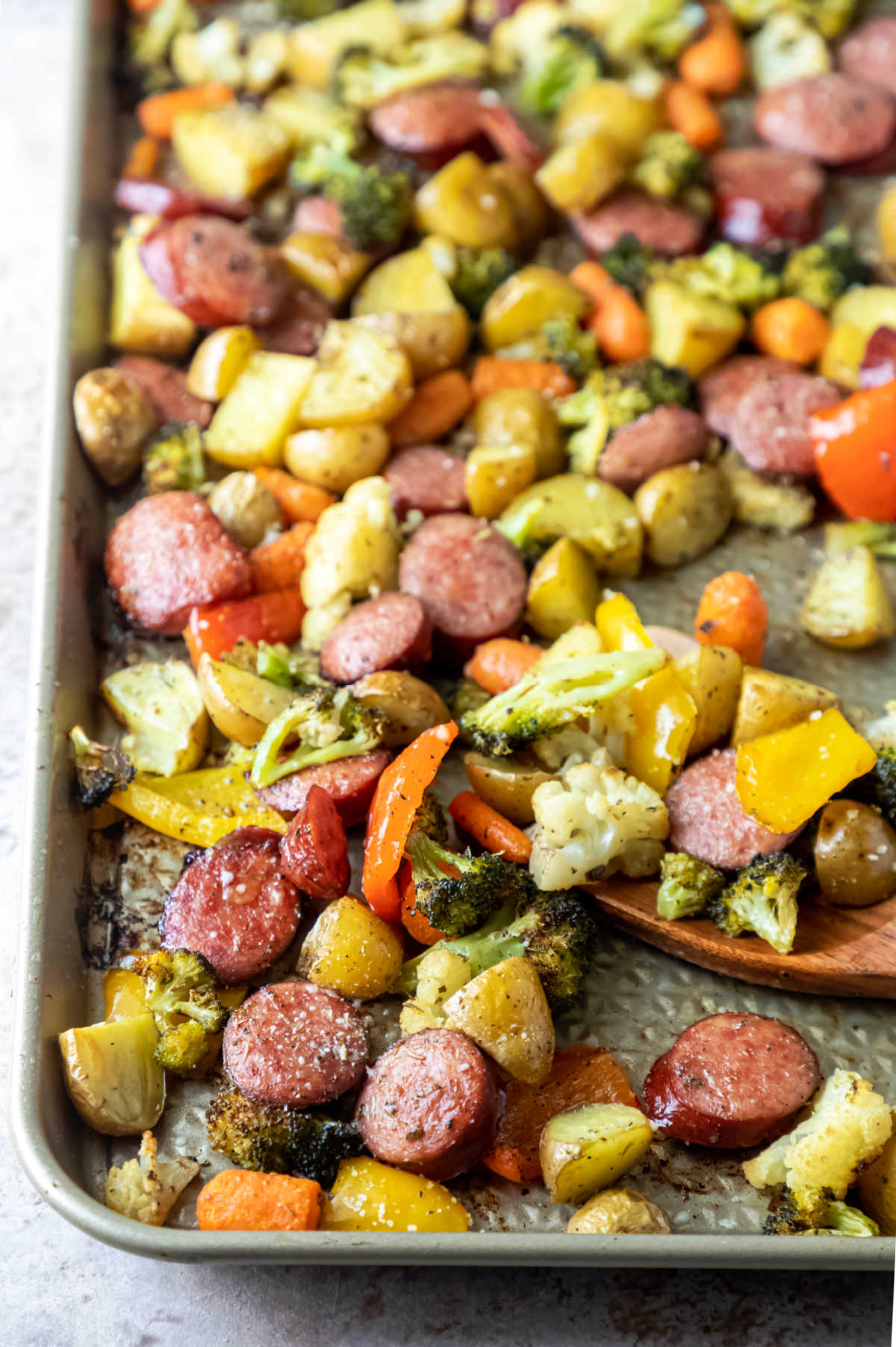 Wooden spoon and roast veggies on a sheet pan.