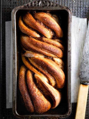 Loaf of cinnamon twist bread in a loaf pan.