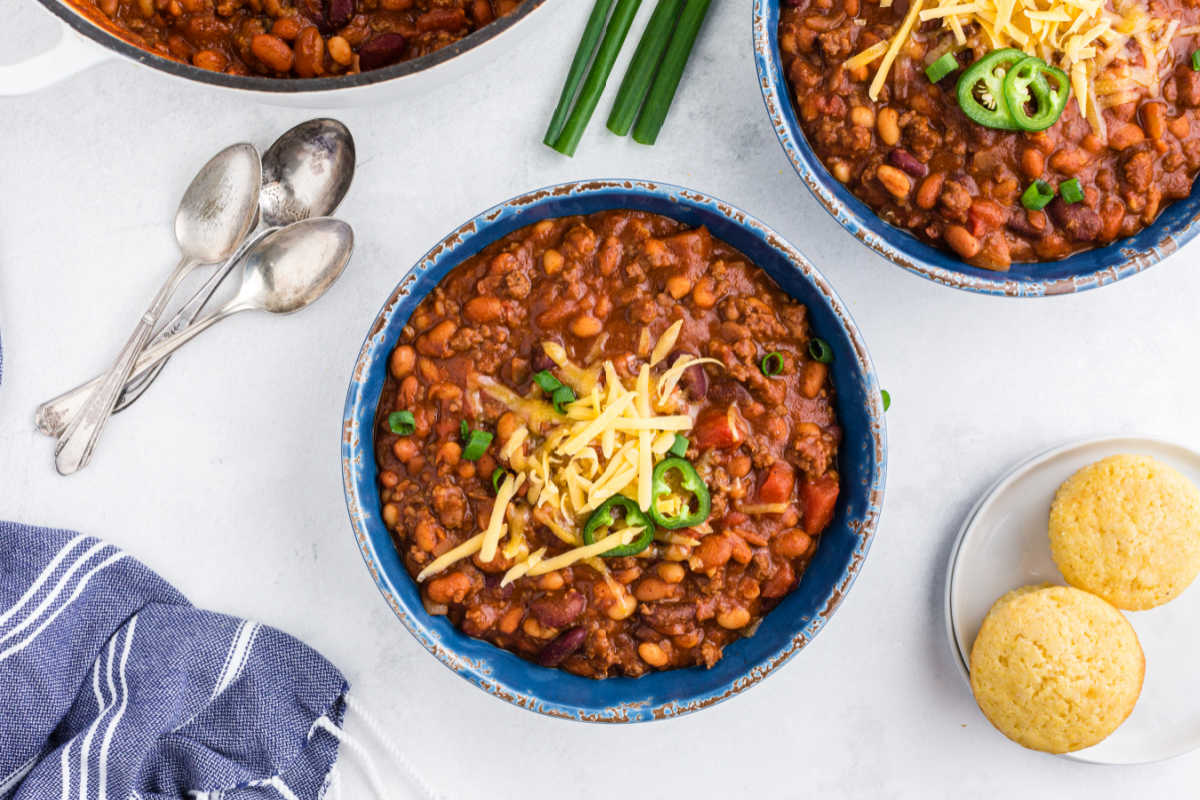 Bowls of chili next to spoons.