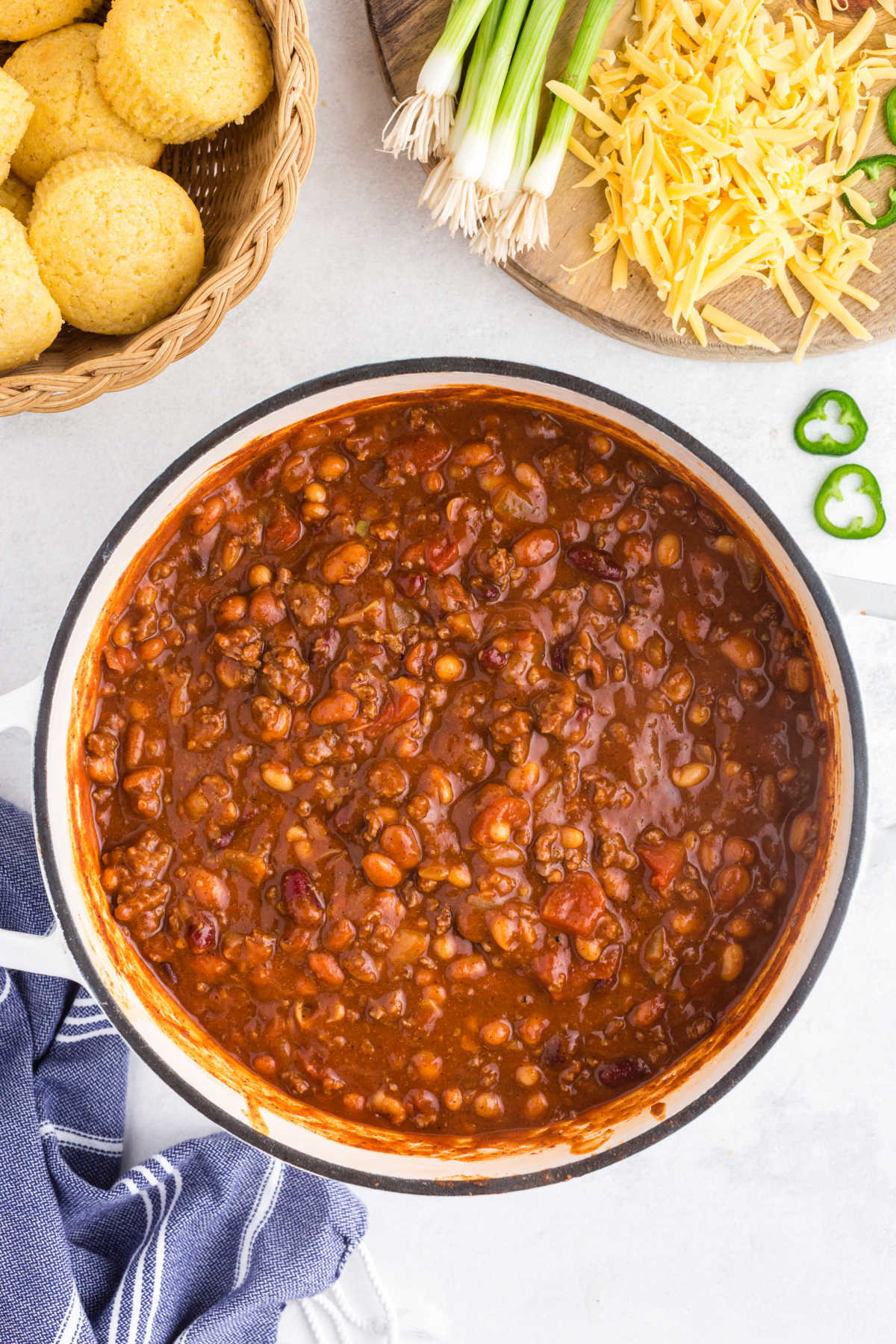 Pot of chili in a Dutch oven next to toppings and cornbread muffins.