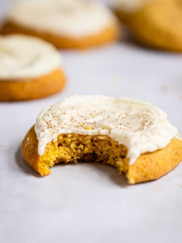 Frosted pumpkin cookie with a bite missing on a piece of white parchment paper.