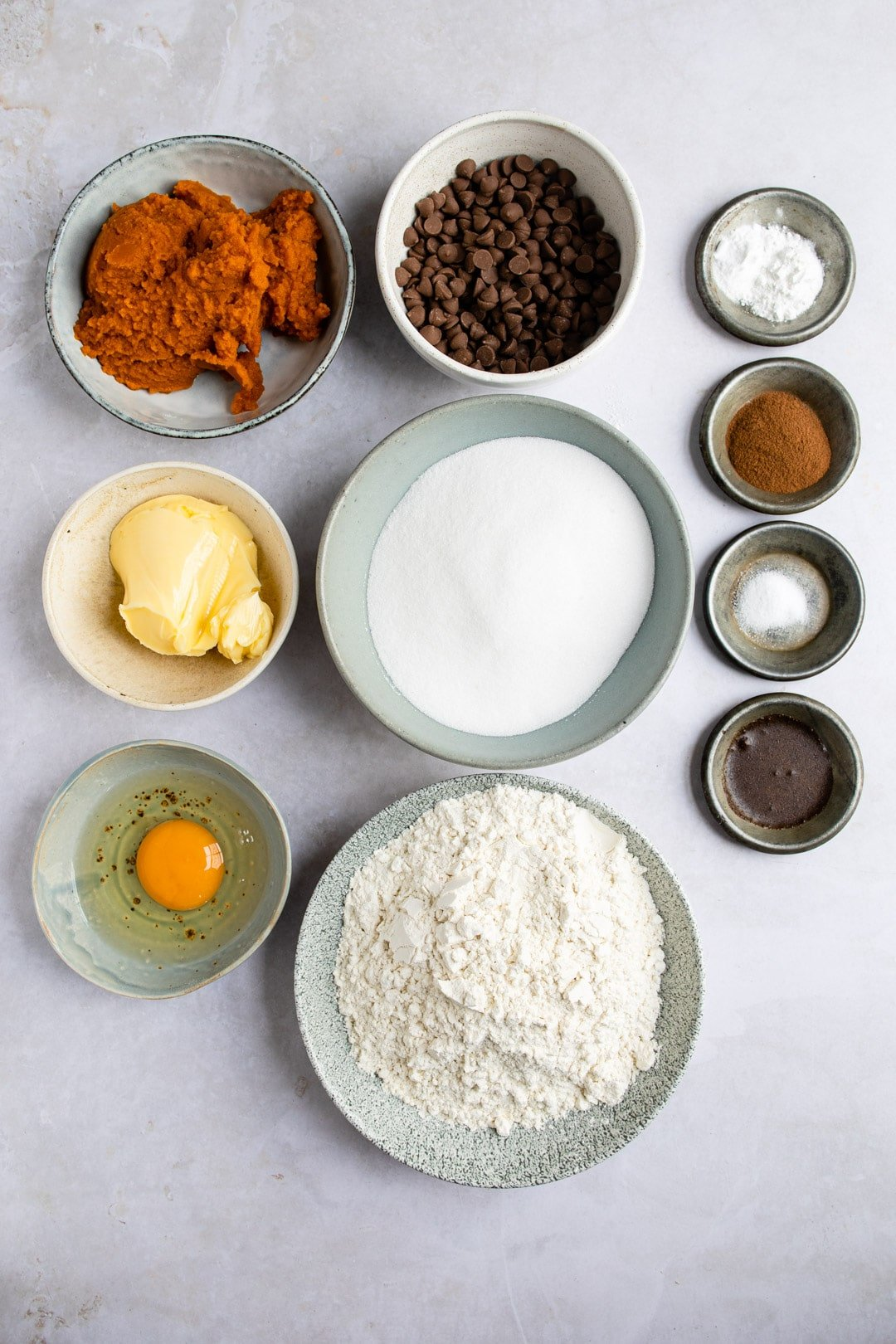 Ingredients for pumpkin chocolate chip cookies on a gray background.