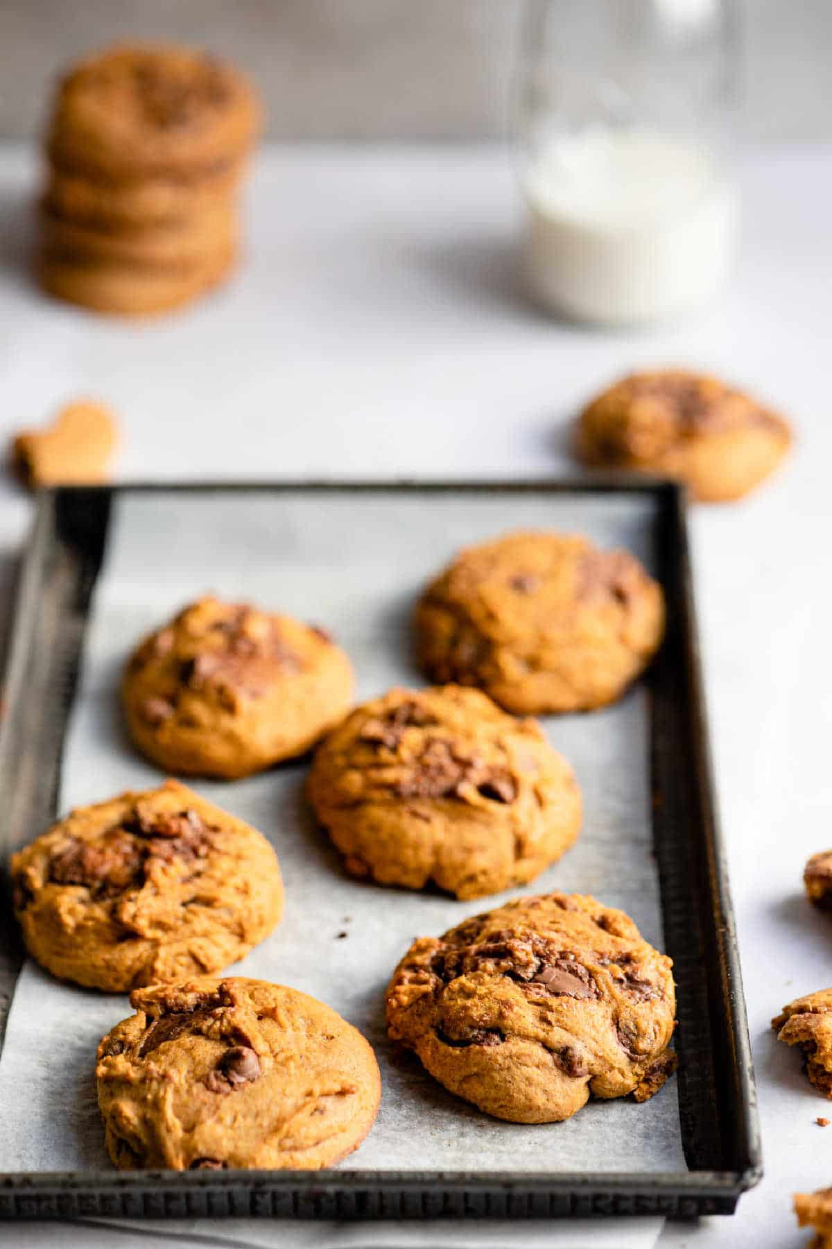 Pumpkin chocolate chip cookies on a baking sheet next to a glass of milk.