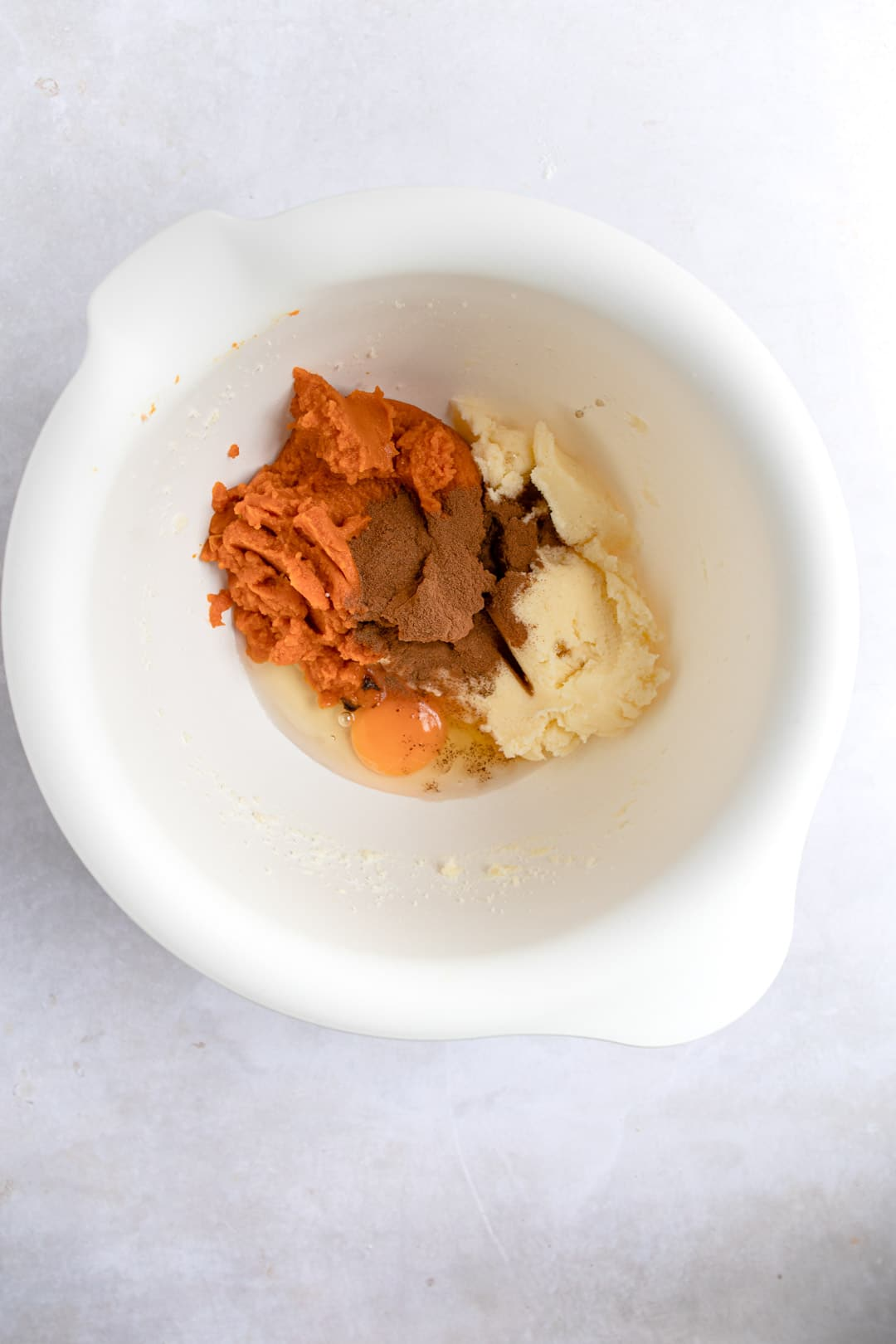 Pumpkin and spices in a white mixing bowl.