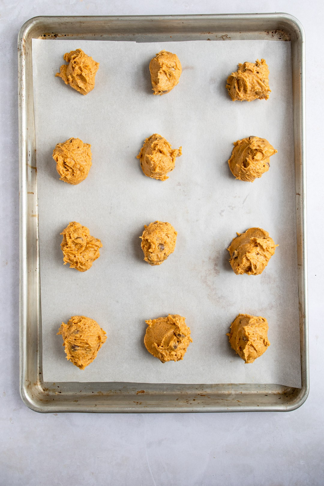 Unbaked pumpkin chocolate chip cookie dough on a cookie sheet.