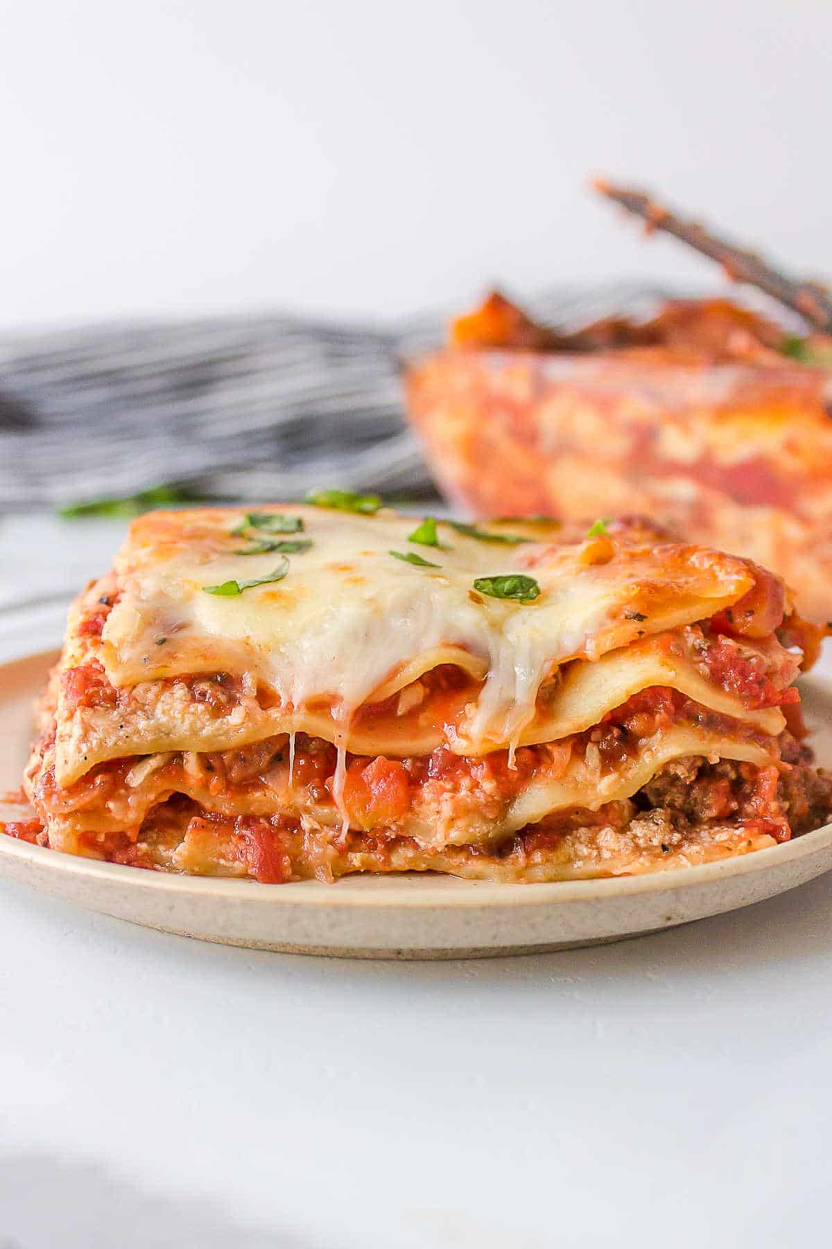 Slice of baked lasagna on a white plate.
