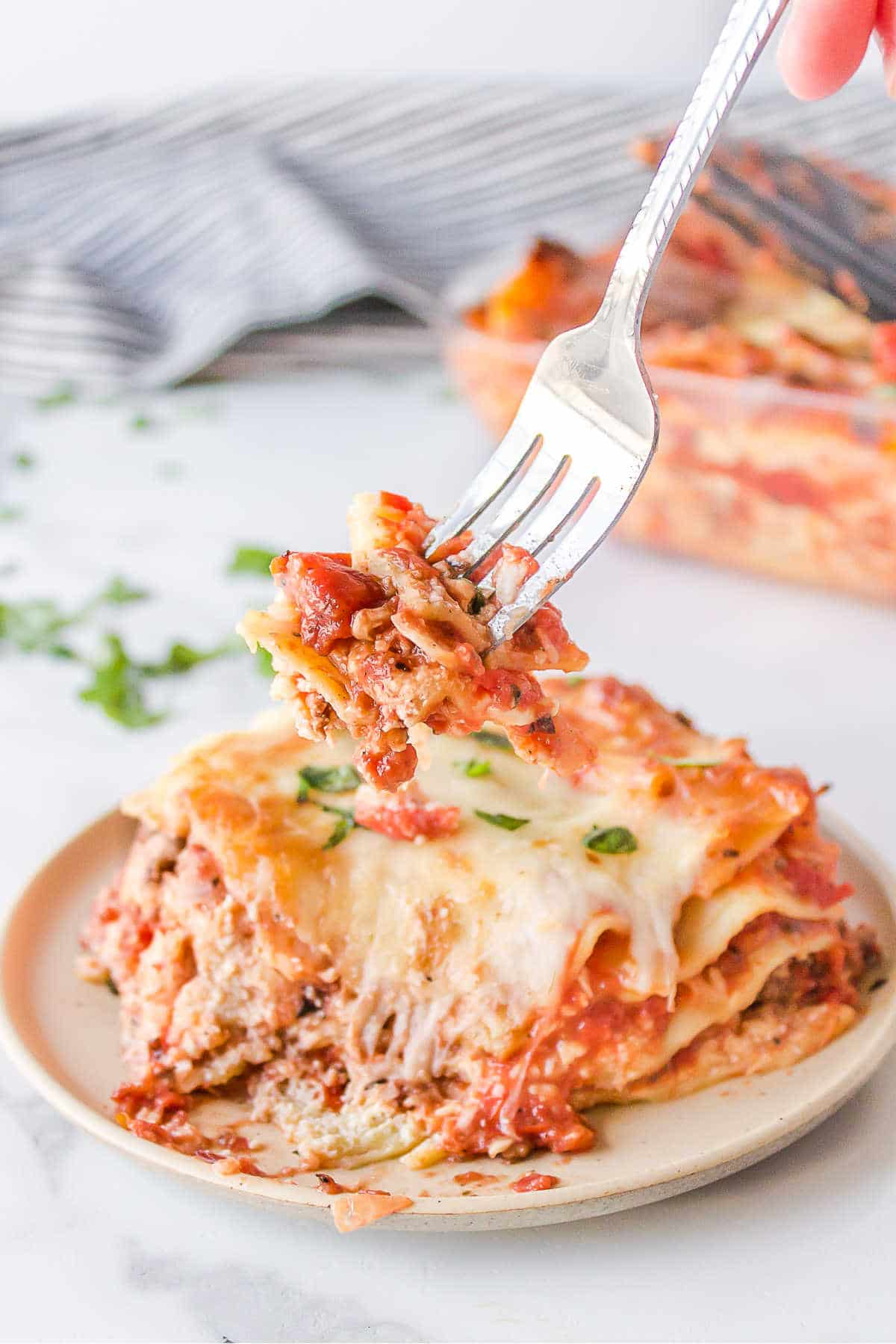 Fork taking a bite from a slice of lasagna.