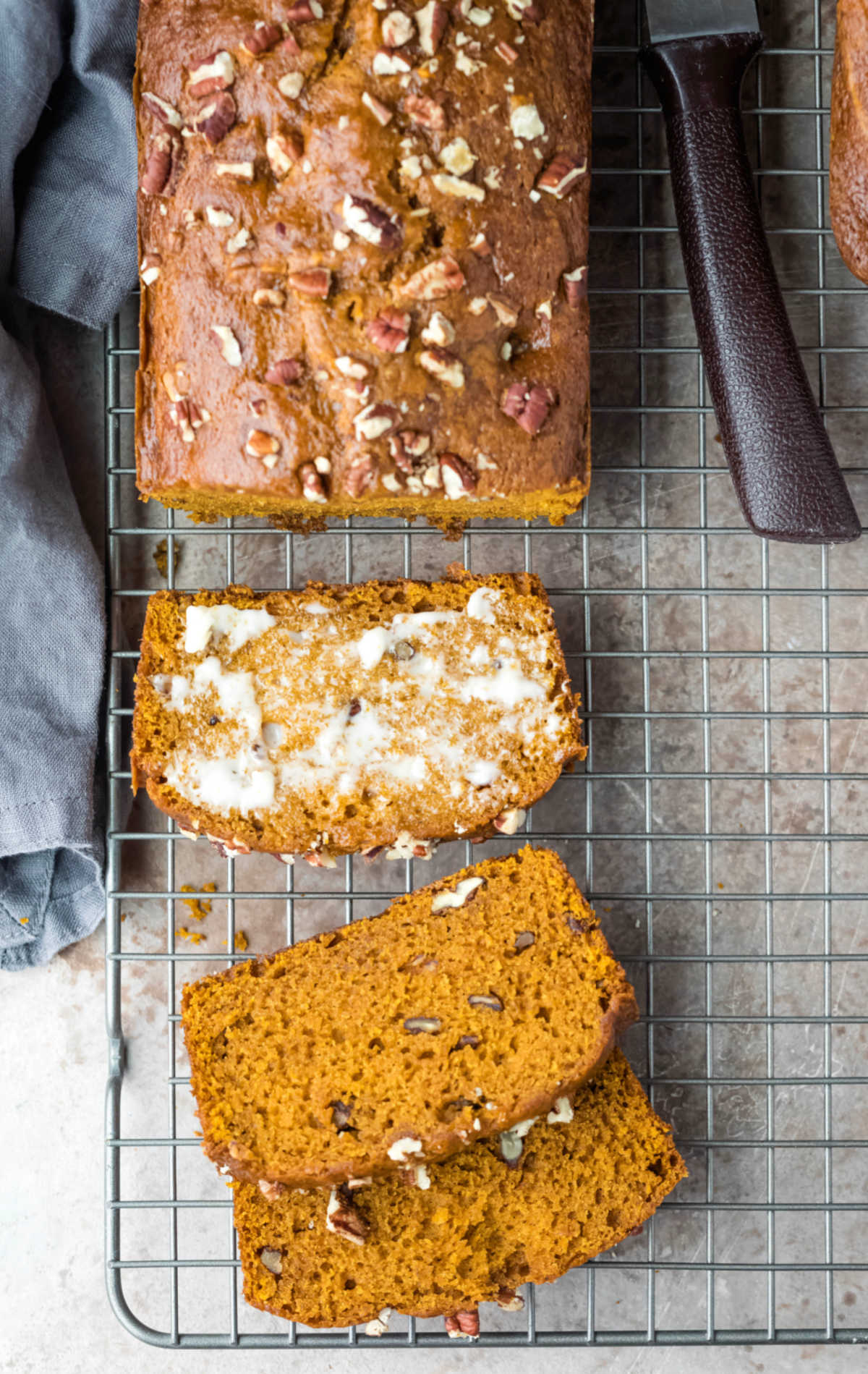A loaf of pumpkin nut bread next to a bread knife.