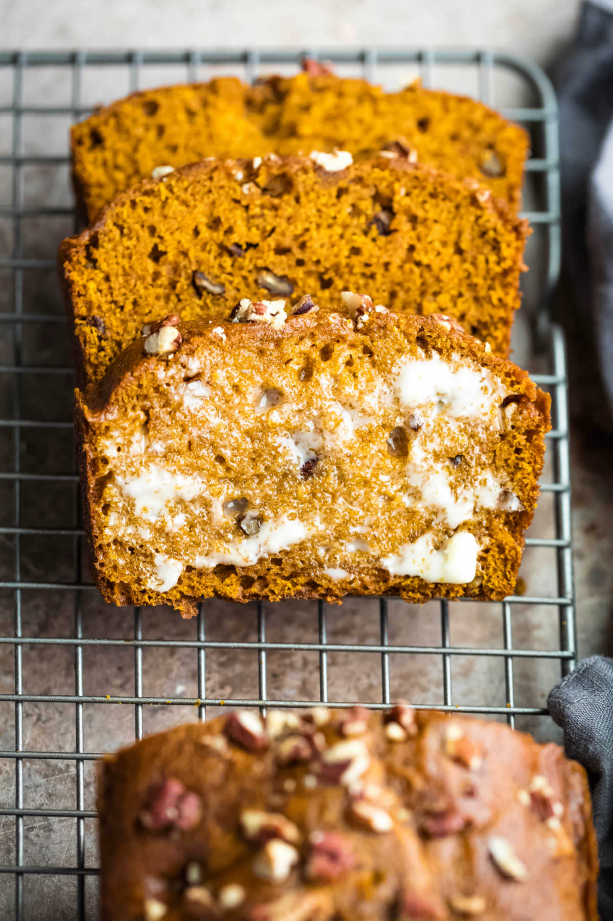 Buttered slice of pumpkin nut bread in a stack.
