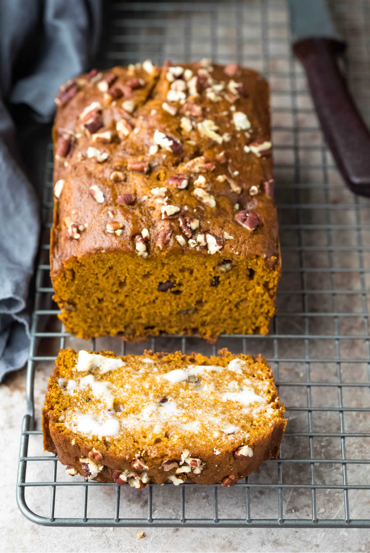 Loaf of pumpkin nut bread with one buttered slice next to it.