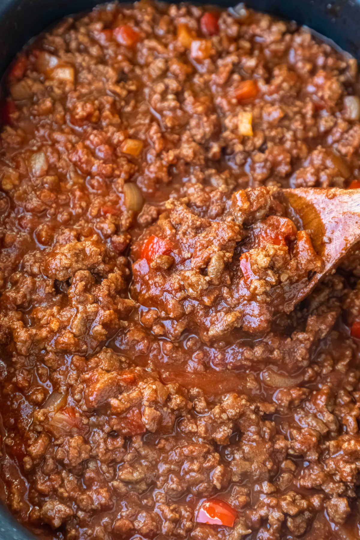 Wooden spoon stirring sloppy joes in a slow cooker.